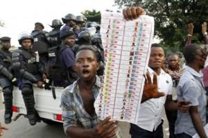 Un jeune homme exibant un bulletin de vote. Source: desc-wondo.org