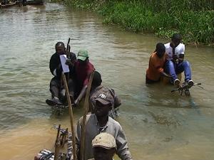 Capture d'écran|Des passagers au dessus des vélos traversant la rivière Kafubu à Lubumbashi.