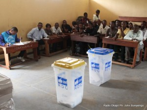 Des témoins des candidats devant les urnes le 28/11/2011 dans un bureau de vote au quartier Makelele dans la commune de Bandalungwa à Kinshasa, pour les élections de 2011 en RDC.   Source: radiookapi.net